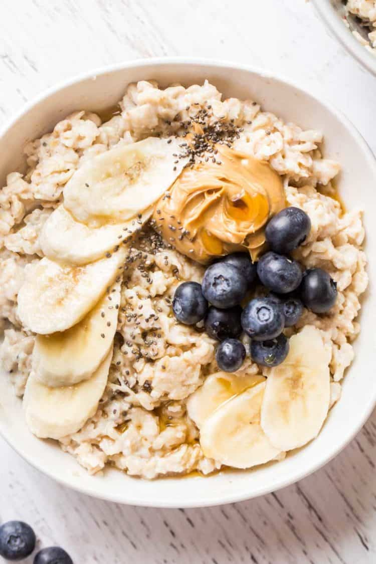 A bowl of homemade oatmeal with bananas, blueberries and peanut butter on top.