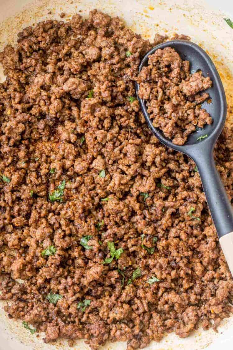 Ground taco meat topped with fresh chopped greens in a white skillet and a spoon.