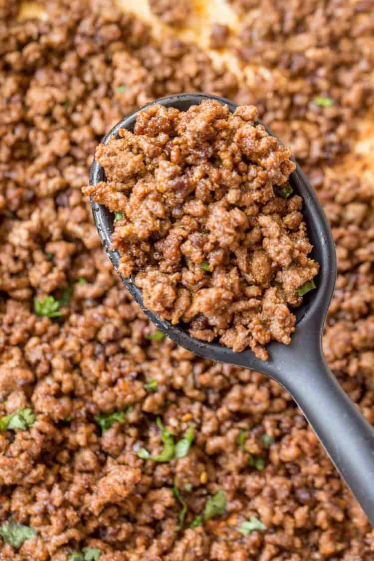Homemade ground beef taco meat in a black spoon in a skillet.