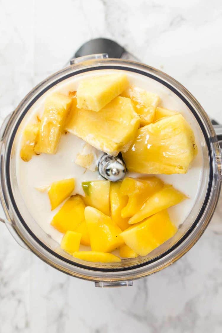 All of the ingredients for a mango smoothie in a blender.