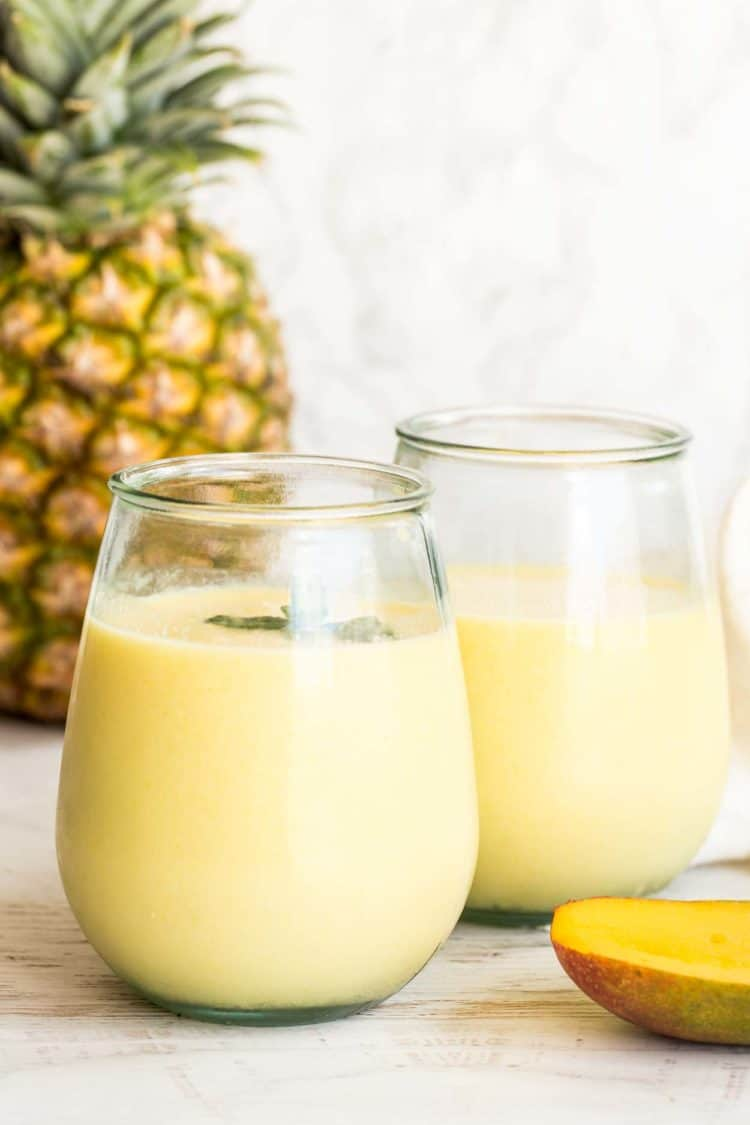 Smootihe in glass cups with pineapple and fresh mango on the side.