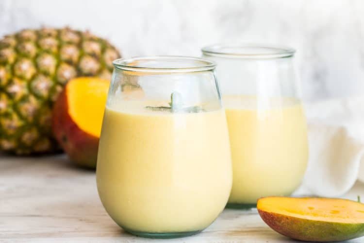 Pineapple mango smoothie in glass jars with fresh mint.