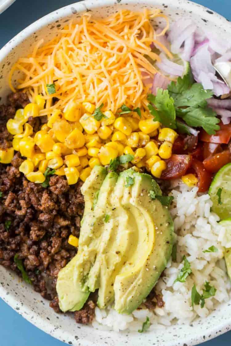 Taco bowl in a white bowl with rice, ground beef, and loaded with toppings.