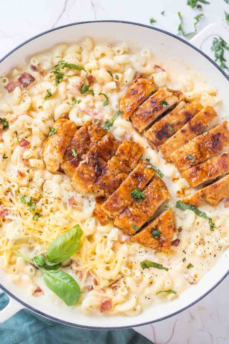 Creamy mac and cheese in a skillet topped with sweet chicken, cheese and fresh greens.
