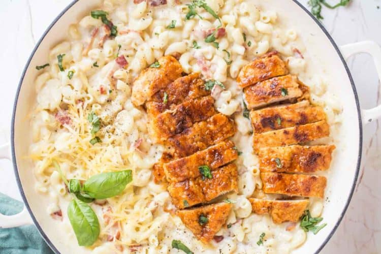 Macaroni and cheese in a skillet with bacon and cheese topped with honey glazed chicken breast.