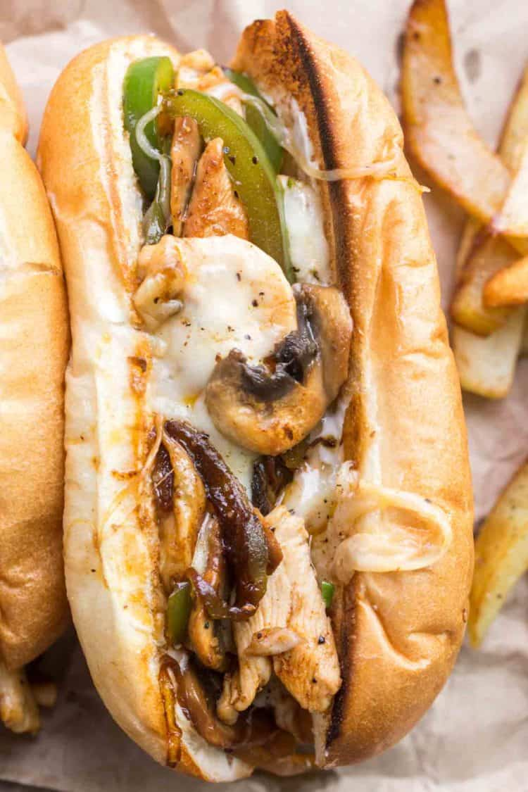 A chicken philly cheese steak sandwich loaded with mushrooms, peppers, loaded cheese.