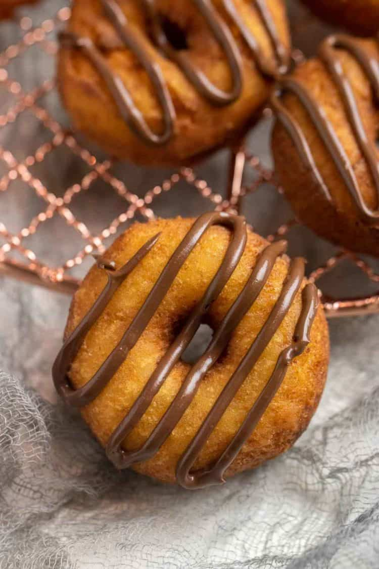 Ricotta donut topped with Nutella drizzle on a cooling rack.