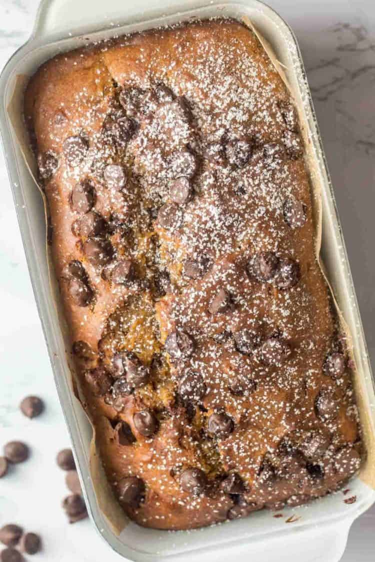 Pumpkin banana bread in a bread loaf toppd with powdered sugar.