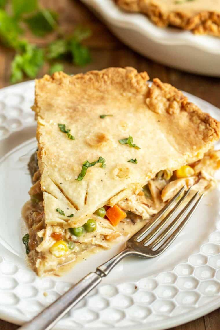 A slice of chicken pot pie on a plate with a fork.