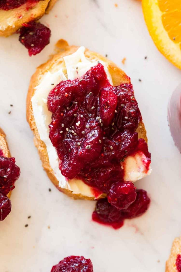 A slice of crispy bread topped with brie cheese and a simple cranberry sauce.