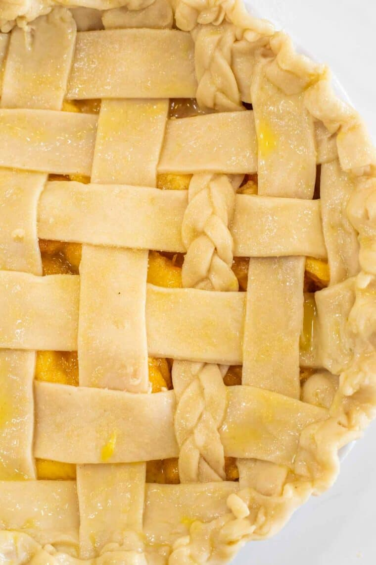 A pie with a lattice pie topping topped with egg yolk and coarse sugar.
