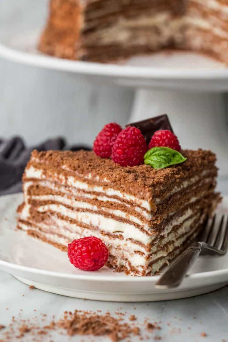 A rich chocolate cake smothered with cream cheese frosting topped with raspberries.