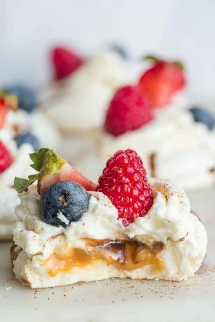 Mini meringue desserts with whipped cream and fresh berries.