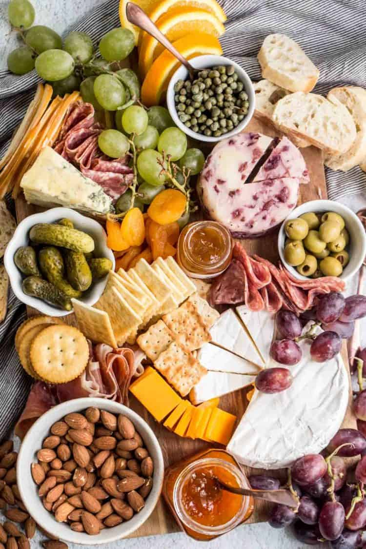 Charcuterie cheese board loaded with cheese, meats, fruits, crackers and side dishes.