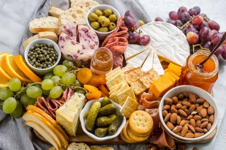 Cheese board loaded with meats, cheese, fruits, nuts and crackers.