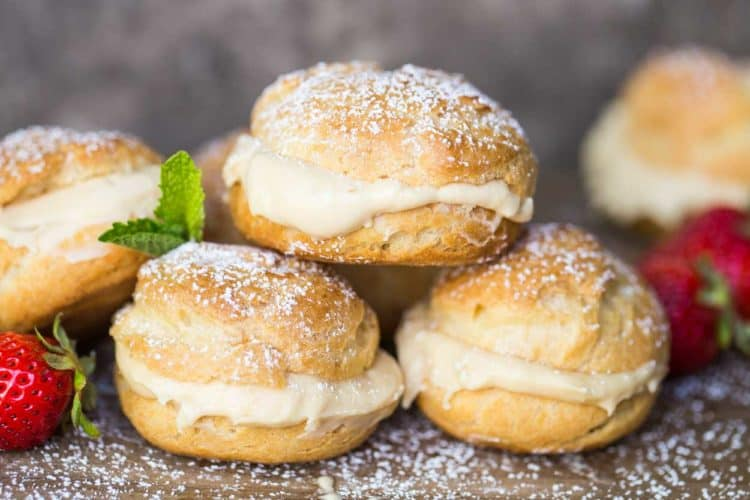 Cream puffs dusted with powdered sugar stacked on top of each other next to strawberries.