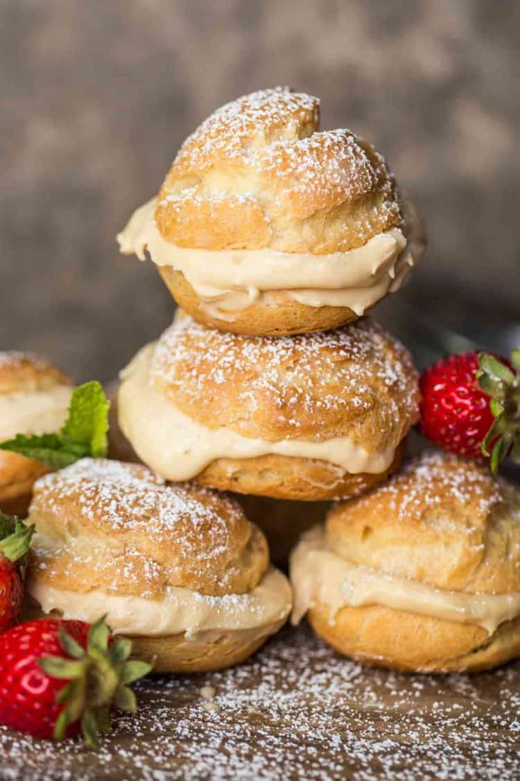 Cream puffs stacked on top of each other topped with powdered sugar.