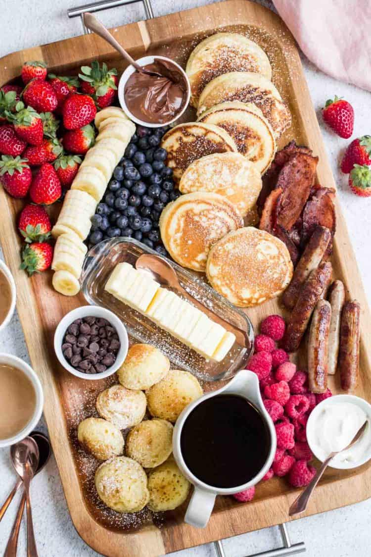 A platter full of pancakes, sausage links, bacon, raspberries, bananas, strawberries, butter, and pancake toppings.
