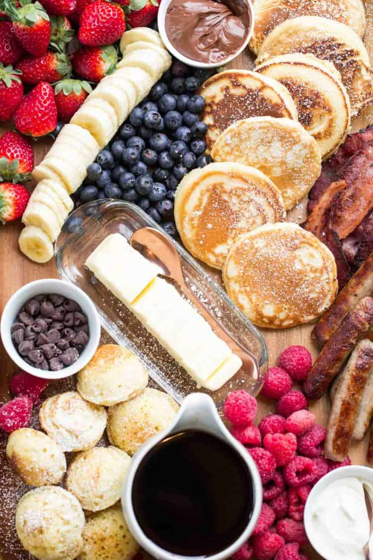 Breakfast charcuterie board filled with moist and airy pancakes with berries and other pancake toppings.