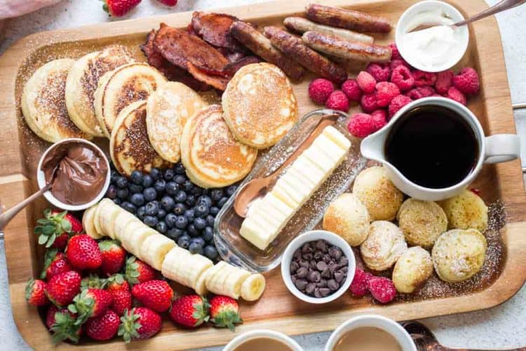 Fluffy homemade pancakes with breakfast meats and all the pancake toppings spread out on a platter.