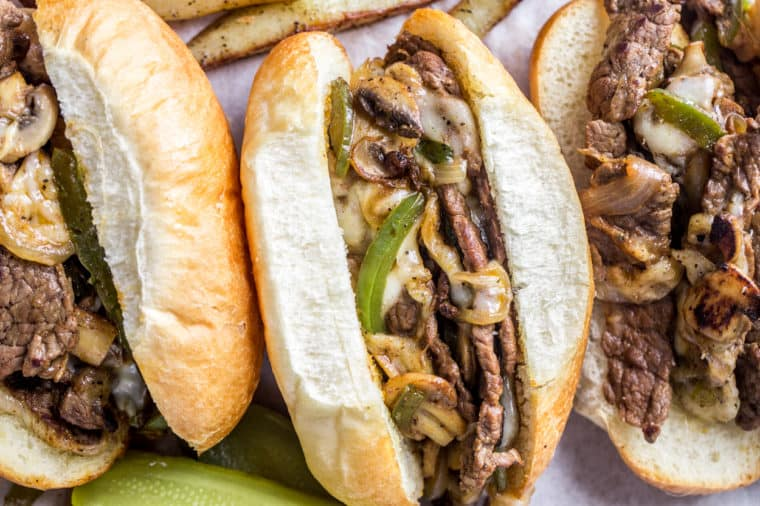 Three philly cheesesteak sandwiches with provolone cheese and chips on a plate.