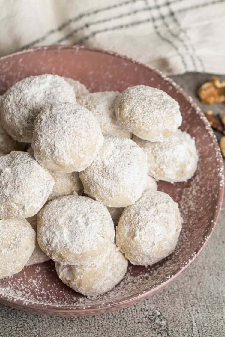 Snowball cookies coated in powdered sugar in a bowl.