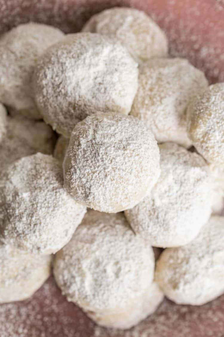 Soft and chewy snow ball cookies on a bowl with powdered sugar.