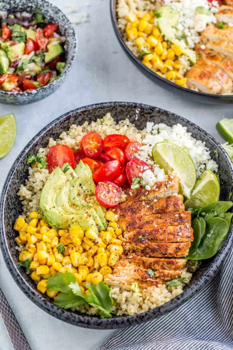 Quinoa bowl loaded with chicken, corn, avocado, tomato, and Feta cheese.
