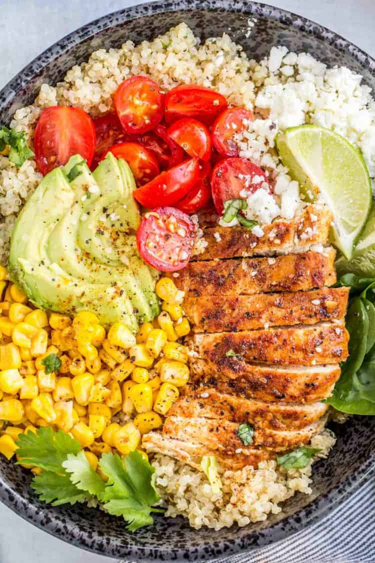 A bowl loaded with quinoa, sliced chicken, tomatoes, corn, and avocado!