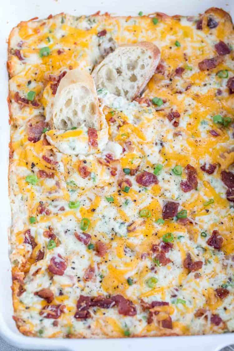 Jalapeno dip made with cheese, bacon, jalapenos, and chicken in a casserole dish.
