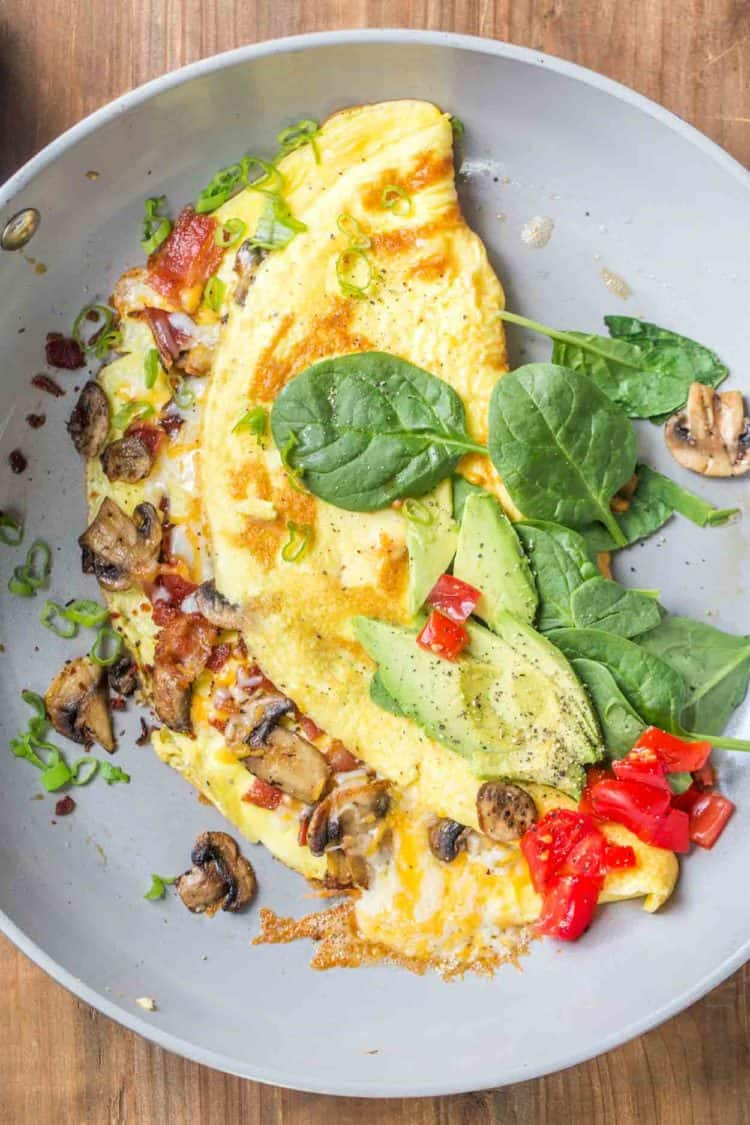 Bacon mushroom omelet on a plate topped with spinach, tomatoes and green onion.