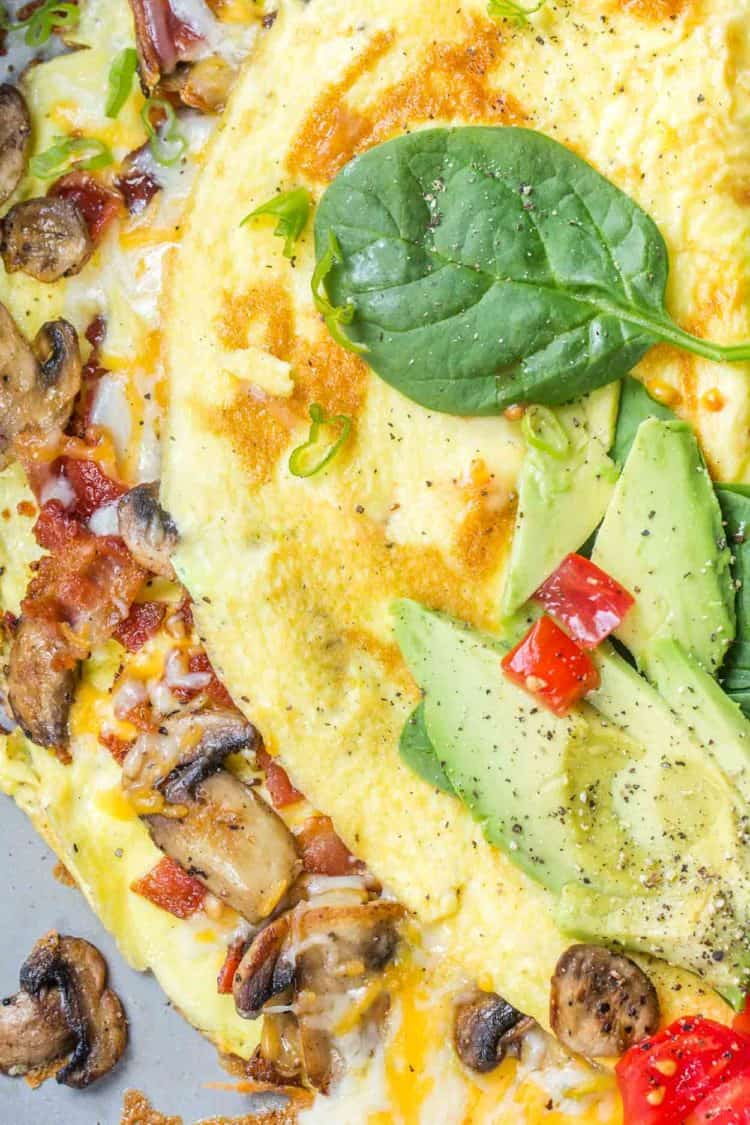 Cheesy omelete loaded with bacon, tomatoes, and bacon on a plate topped with avocado and spinach.
