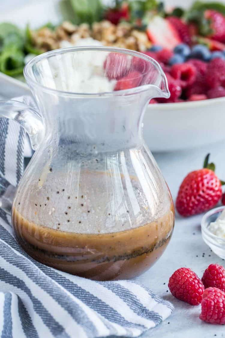 Homemade poppy seed dressing in a glass jar with a bowl of salad behind it.
