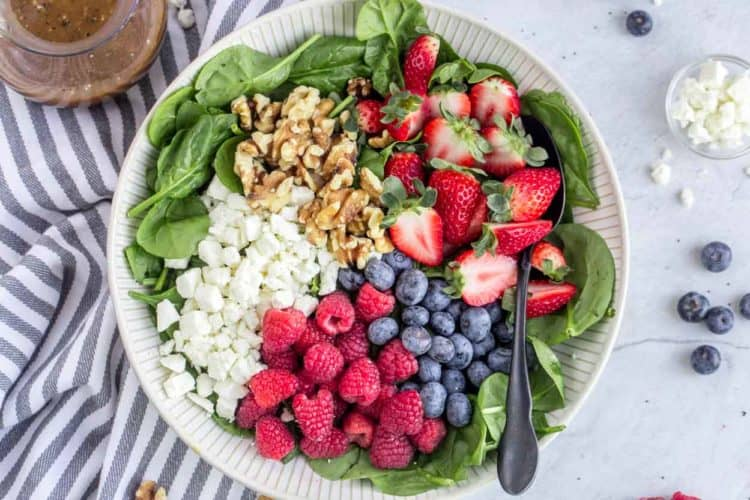 A bowl loaded with spinach, Feta cheese, walnuts and fresh berries.