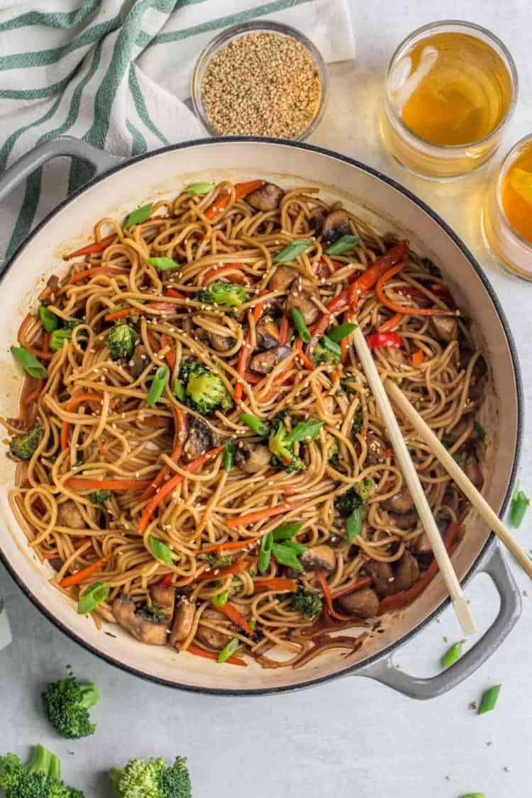 Vegetable lo mein in a skillet with chop sticks next to two glasses of tea.