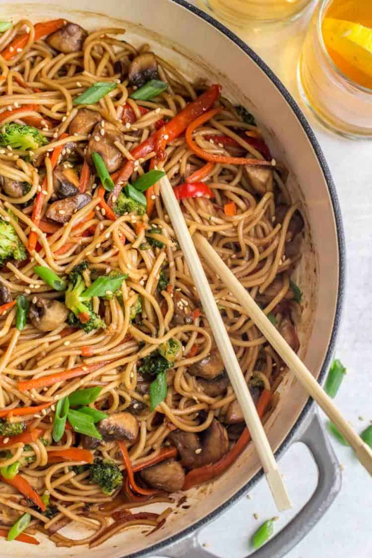 Lo mein in a pan with chop sticks topped with fresh greens and sesame seeds.