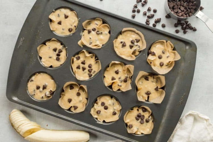 Banana chocolate chip muffin batter in muffin liners in a muffin pan.