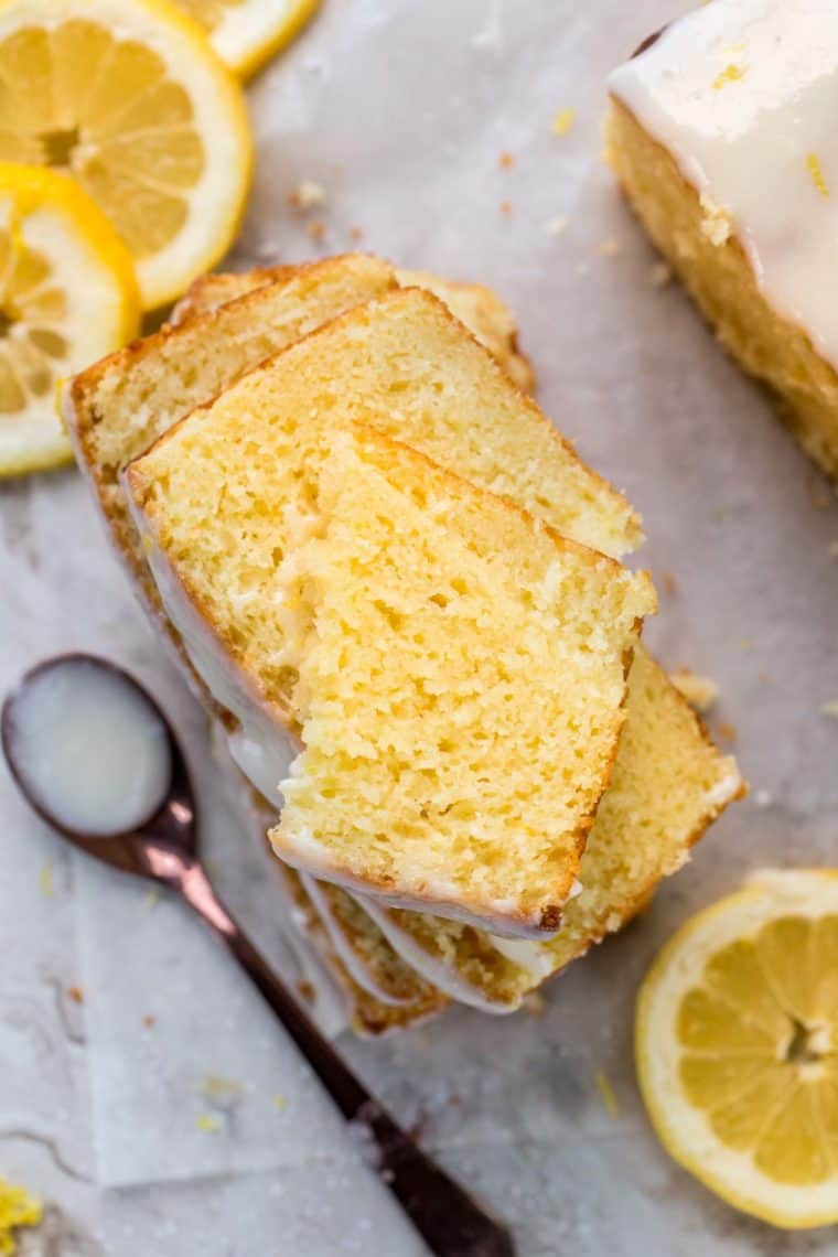Sliced of lemon bread stacked on top of each other next to a spoonful of glaze and lemons.