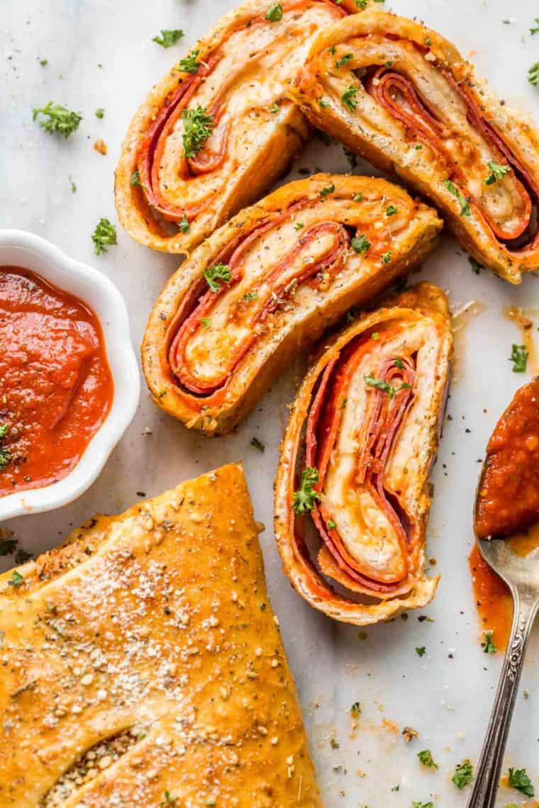 Stromboli pizza sliced into four pieces next to marinara sauce and topped with fresh greens.