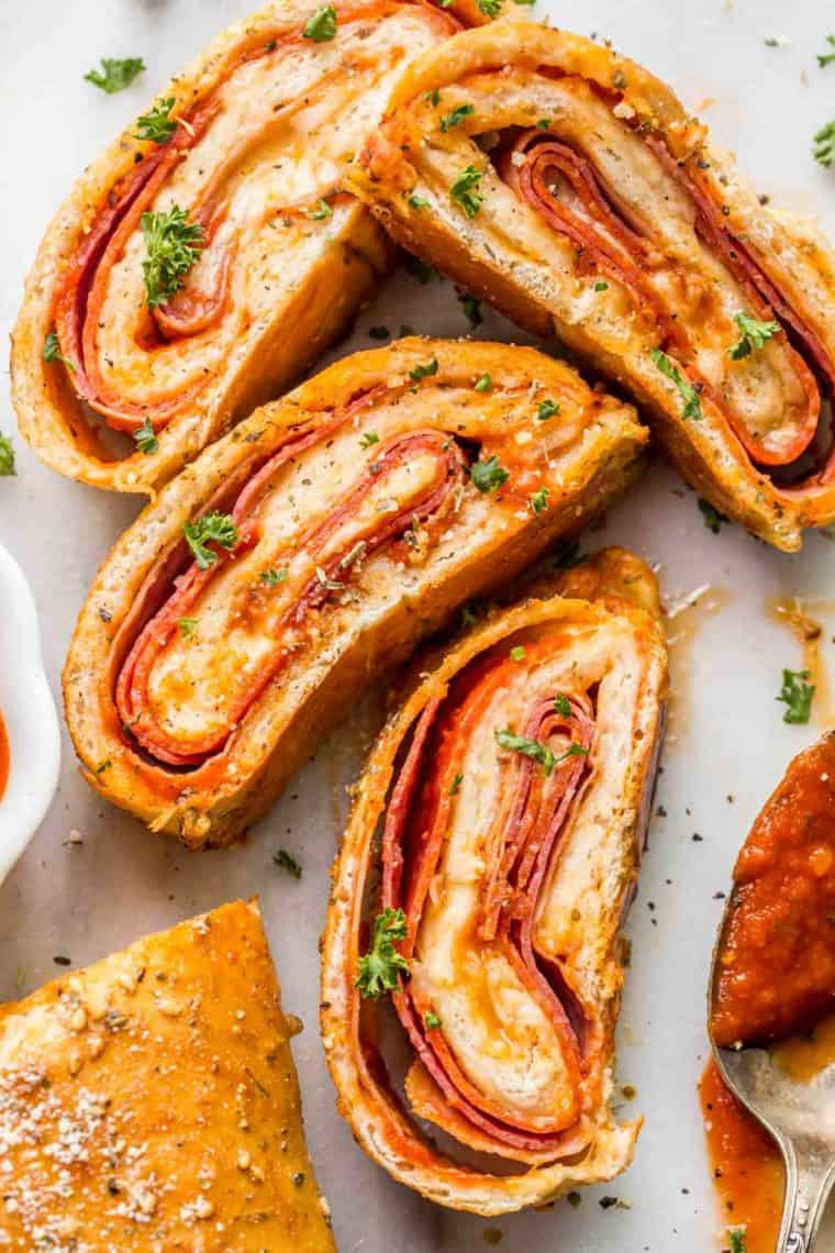 Four slices of Stromboli topped with shredded parsley next to a spoon of marinara sauce.