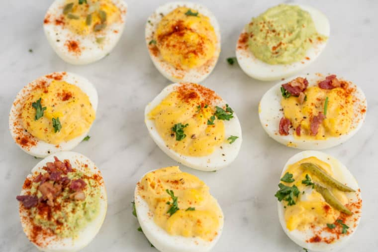 Deviled eggs topped with bacon, fresh greens, and paprika.