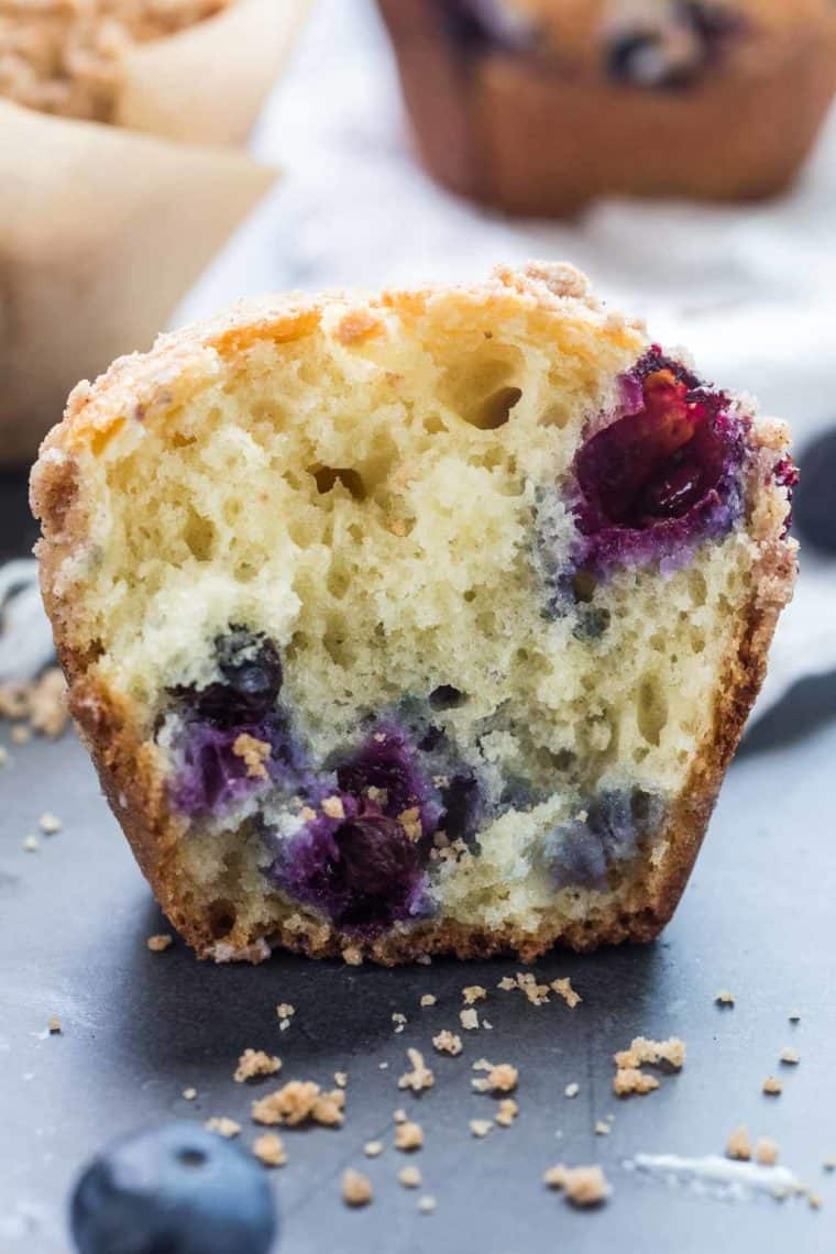 A blueberry muffin cut in half loaded with fresh blueberries.