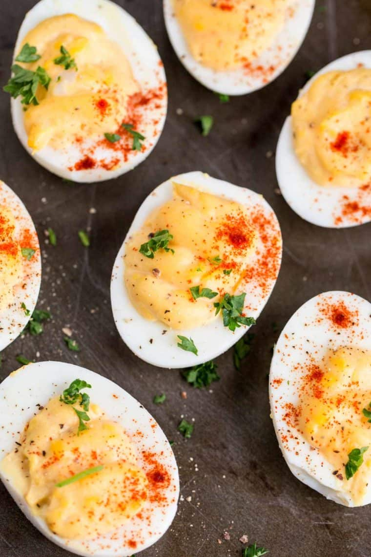 Deviled eggs on a platter topped with fresh greens and ground paprika.