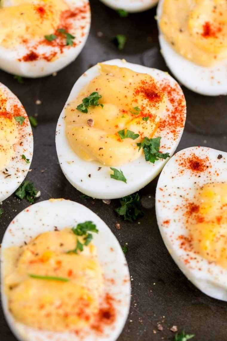 Hard-boiled egg whites filled with a creamy egg yolk mixture topped with seasoning and fresh greens.
