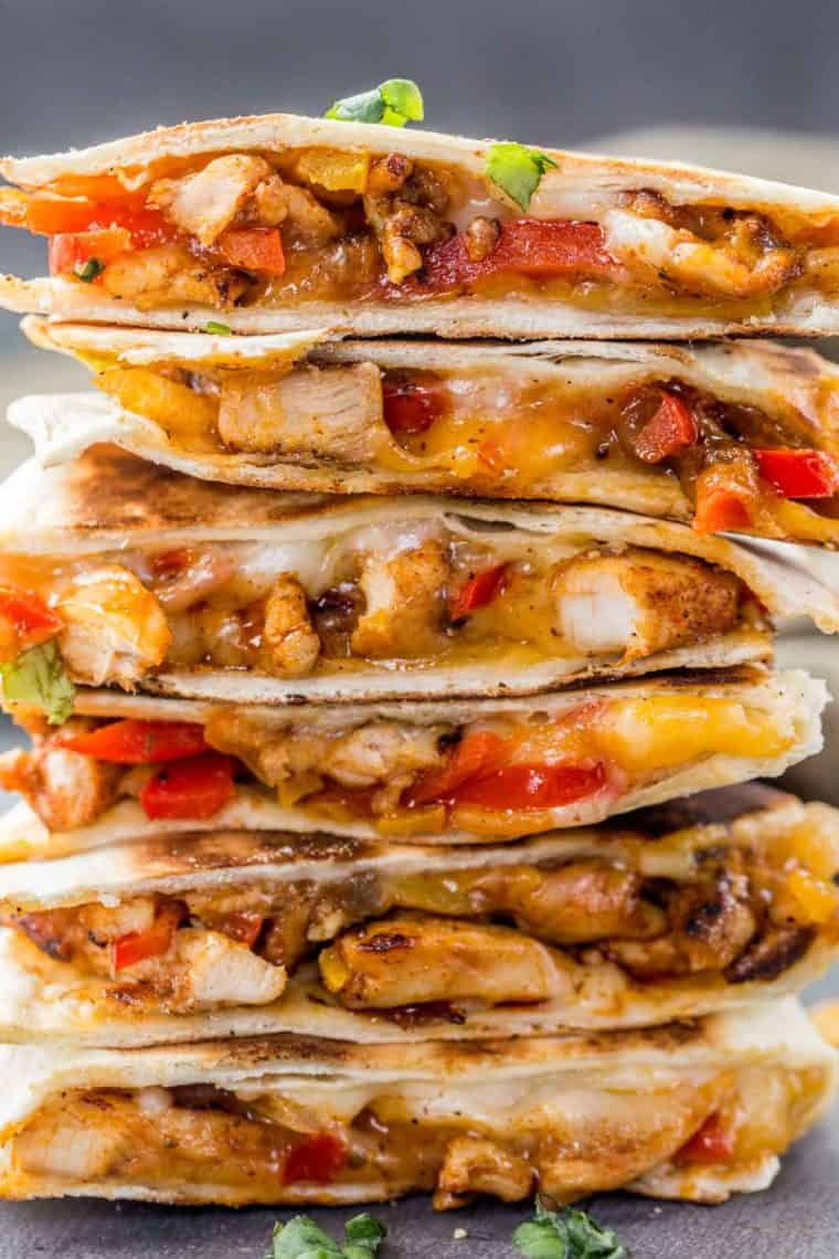 Cheesy chicken quesadillas stacked on top of each other topped with fresh greens.