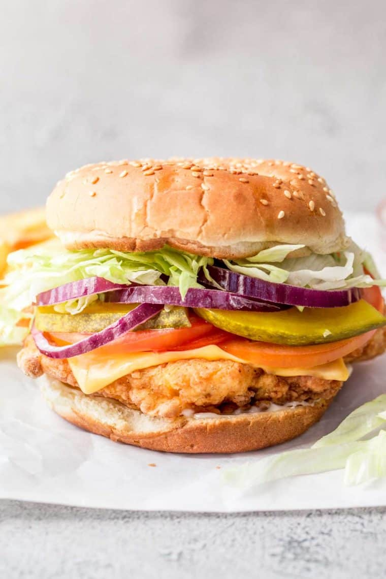 Crispy chicken sandwich loaded with vegetables and cheese on parchment paper.