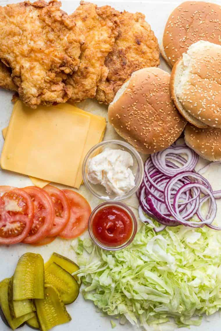 Crispy chicken sandwich, buns, cheese, mayo, ketchup, lettuce, tomatoes, and pickles on a platter for this chicken sandwich recipe.