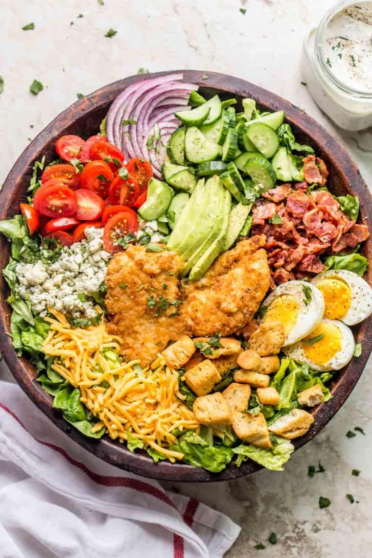 Cobb salad in a brown bowl topped with fresh greens next to a rag and a jar of homemade ranch.
