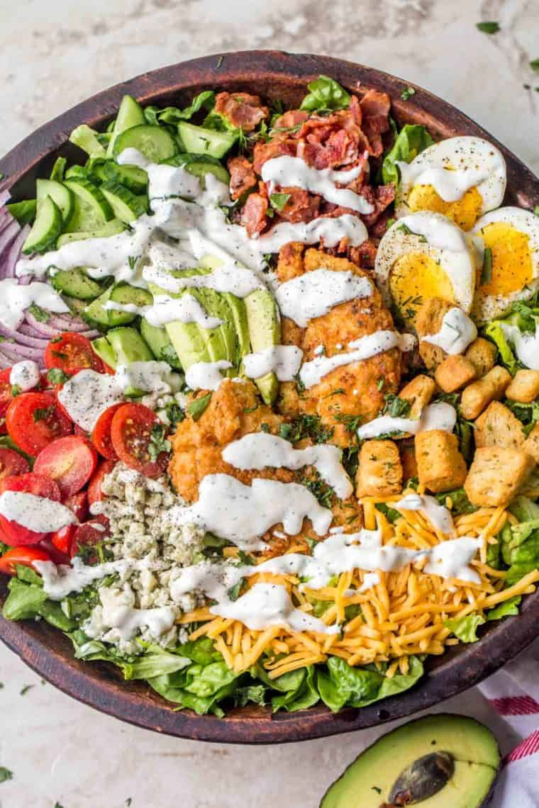 A brown bowl loaded with lettuce, bacon, egg, chicken, tomatoes, croutons and drizzled in homemade Ranch dressing.