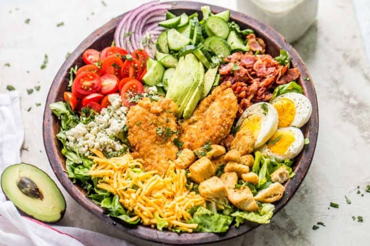 Cobb salad topped with fresh greens next to a white rag, an avocado, and a jar of Ranch.